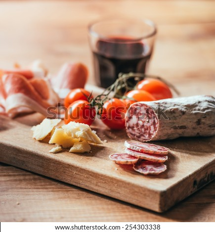 Appetizers - tomato, meat and cheese - on wooden board with  glass of wine - stock photo