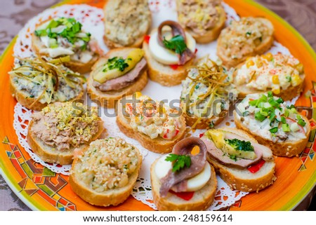 Appetizers with cheese and ham vegetables on  festive table - stock photo