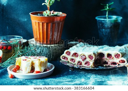 Appetizing baked apples stuffed with raisin and nuts. Baked apples with sweet jam raspberry jam and walnuts on the metal pan. Fresh herbal tea with red berries in glass. Rustic dark style.