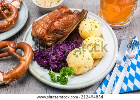 Appetizing Bavarian roast pork dish with dumplings and pretzel