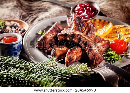 Appetizing BBQ Boar Spare Ribs with Grill Marks Served on Platter with Grilled Fruit and Sauces in Rustic Woodsy Still Life - stock photo