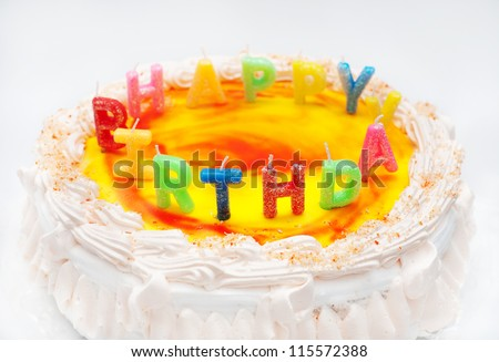 """appetizing birthday cake with the light colorful candles with text """"happy birthday"""" - stock photo"""
