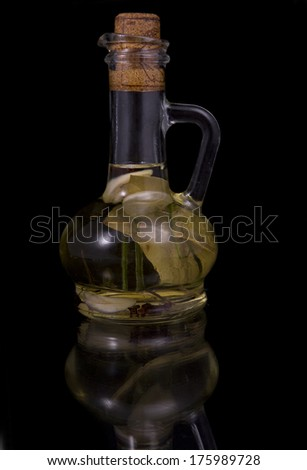 appetizing bottle of olive oil infused with spices, garlic and bay leaf on a black background