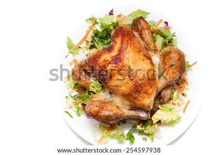 Appetizing crispy red roasted spicy grilled chicken with vegetable garnish on white plate on isolated white background