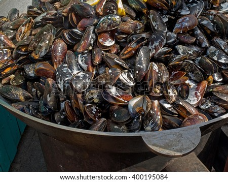 Appetizing delicious fried seafood mussels cooked fried in a cauldron outdoors. Selective focus - stock photo