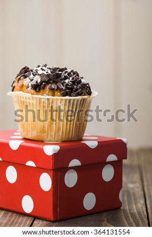 Appetizing delicious traditional fresh baked cupcake decorated by chocolate in paper case standing on bright red with white dots box beautiful package on light background indoor closeup, vertical  - stock photo