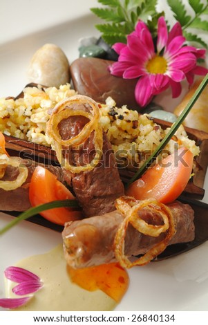 Appetizing dish from meat with a flower - stock photo