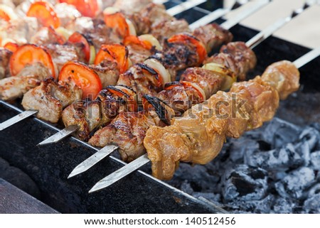 Appetizing fresh meat shish kebab (shashlik) prepared on a grill wood coal, outdor