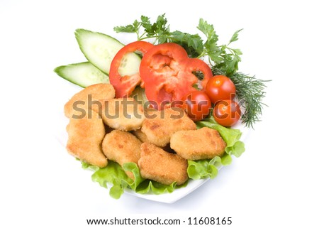 Appetizing fried chicken nuggets  with tomatoes, cucumber and pepper on salad leaves. Close-up. Selective focus. - stock photo