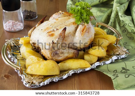 Appetizing fried chicken or a turkey on a silver tray with fried potato slices on rustic wooden table salt and pepper - stock photo