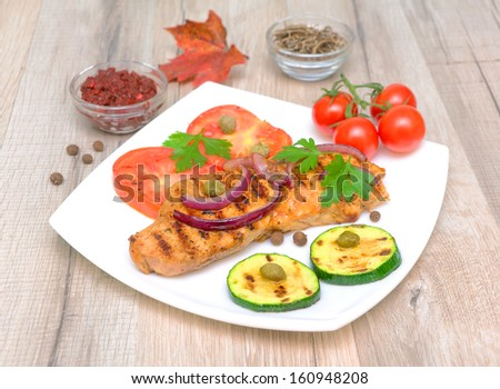appetizing fried meat on a grill with vegetables on a wooden table. horizontal photo.