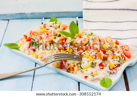 Appetizing healthy rice with vegetables in white bowl on a wooden background  with basil leaves - stock photo