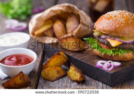 Appetizing homemade burger with beef patty, lettuce, tomato, cheese, pickled cucumbers and red onion served with fried potato, white sauce and ketchup, on wooden cutting board. Close up view - stock photo