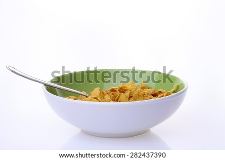 Appetizing krispy of cereal cornflakes with frosting in light green plate and spoon on white background copy space, horizontal photo - stock photo
