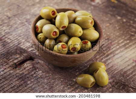 Appetizing olives stuffed with red pepper  in bowl on wooden background. Rustic style. Selective focus. - stock photo