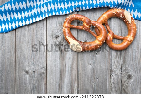 Appetizing pretzels with a bavarian flag  on wooden background - stock photo