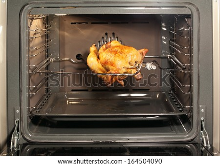 Appetizing roast chicken in the oven. - stock photo