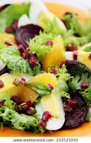 appetizing salad with vegetables, eggs and orange