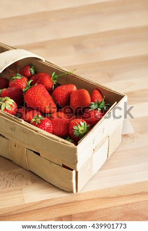Appetizing strawberries in a pottle on a wooden table.