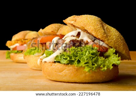 Appetizing veggie, fish and beef burgers  served on a rustic wooden board  - stock photo