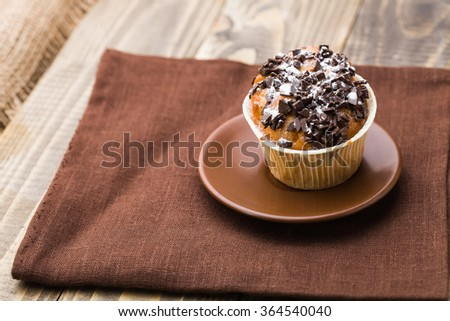 Appetizing warm homemade beautiful muffin with chocolate chips and white sugar powder in paper case on brown saucer standing on dark fabric on wooden background indoor closeup, horizontal picture - stock photo