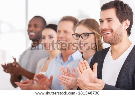Applauding to corporate innovations. Group of cheerful business people applauding to someone  while standing in a row  - stock photo