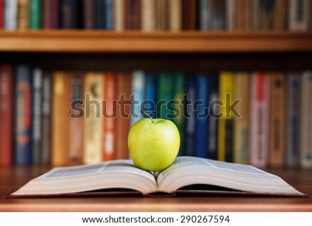 apple and book on background bookshelf - stock photo