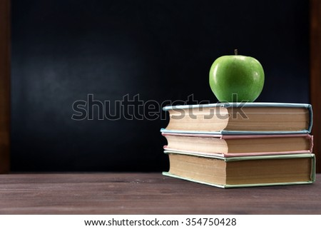 Apple and books on desk background - stock photo