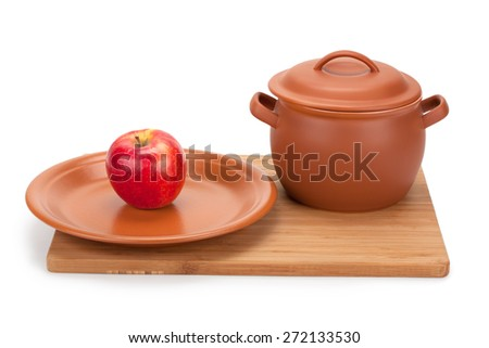 apple and earthenware crockery on a cutting board isolated on white background - stock photo