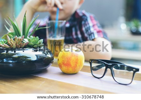 Apple and glasses in front of little boy. - stock photo