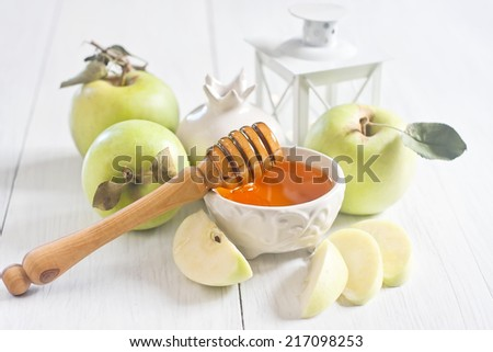Apple and honey, traditional food of jewish New Year celebration, Rosh Hashana. Selective focus. High key.