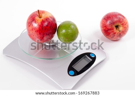 apple and lemon on kitchen scale isolated on white background