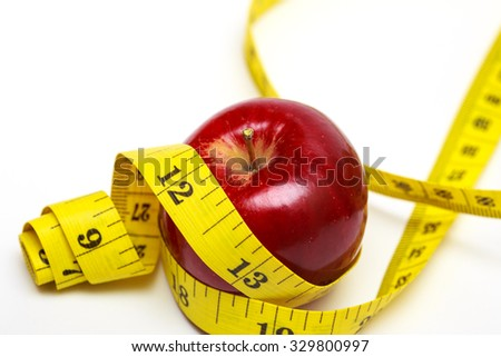 apple and measuring tape on a white background