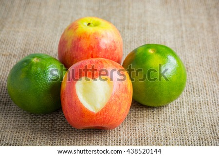 Apple and orange on hemp sack background. Concept Healthy fruit, weight lose, diet. - stock photo