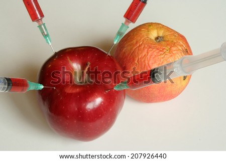 Apple and Orange with syringes. Genetically modified food. - stock photo