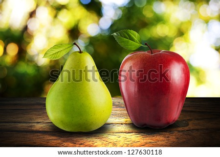 Apple and Pear on wood with summer scene background - stock photo