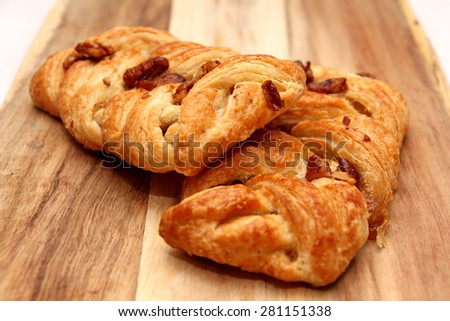 Apple and Pecan plait danish pastry on wooden board - stock photo