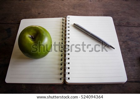 Apple and pen on notebook,Still life photography