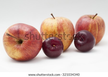 apple and plums isolated on white - stock photo