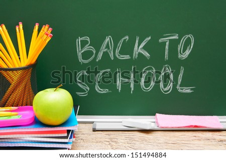 Apple and school accessories against a school board. Back to school. - stock photo