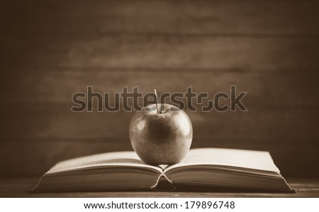 Apple and the book. Photo in old color image style - stock photo