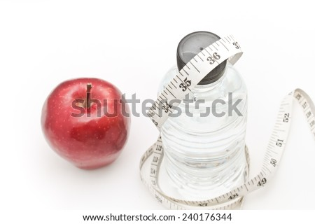 Apple and water. Tape measure waist as a symbol of diet. - stock photo