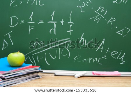 Apple and writing-books against a school board (the formula on the physicist). - stock photo