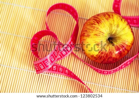 apple annd measuring tape as elements for weight loss - stock photo