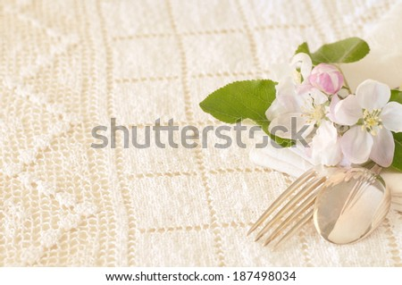 Apple Blossoms with Fork and Spoon on Table with Cream Lace Tablecloth.  Above View horizontal with room or space for text, copy.  Vintage camera treatment. - stock photo