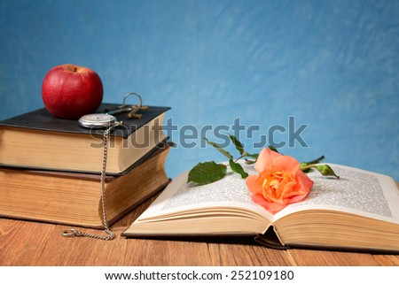 Apple, books and pocket clock on the table - stock photo