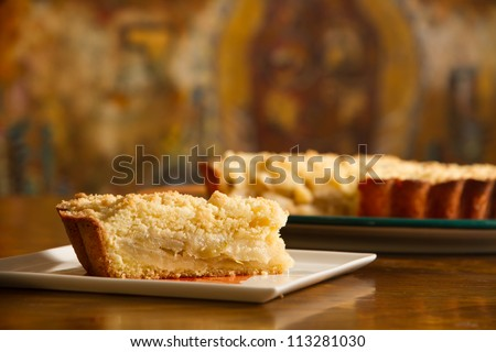 Apple cake portion with the rest of the cake of substance. - stock photo