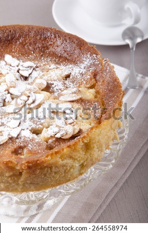 apple cake with almond sliver and powdered sugar on a cake stand