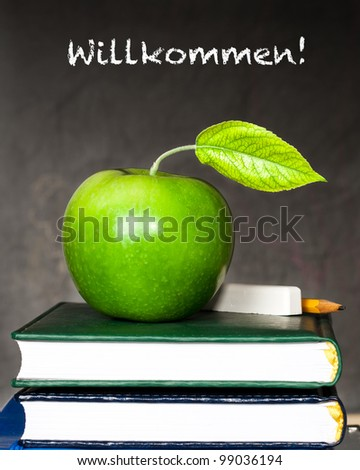 """Apple, chalk and pencil on textbooks against blackboard with text """"Welcome!"""" in the German language. School concept - stock photo"""