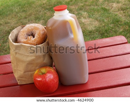apple cider, an apple and a bag of cinnamon-sugared donuts on a red picnic table - stock photo